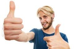 Homem novo satisfeito que dá o polegar acima Imagens de Stock