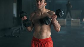 Homem novo saudável que faz o exercício para o bíceps Halterofilista novo que faz o exercício pesado para o bíceps movimento 4k l filme