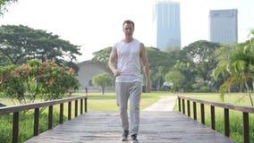Homem novo saudável que movimenta-se para a ponte de madeira no parque filme