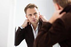 Homem novo seguro à moda que olha si mesmo no espelho imagens de stock