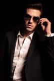 Homem novo 'sexy' da forma que põe sobre seus óculos de sol imagem de stock royalty free
