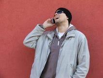 Homem novo 'sexy' na fala vermelha do telefone do fundo Fotografia de Stock Royalty Free