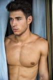 Homem novo 'sexy' que está descamisado por cortinas Fotos de Stock Royalty Free