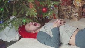 Homem novo sonolento perto da árvore de Natal video estoque