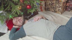 Homem novo sonolento perto da árvore de Natal filme