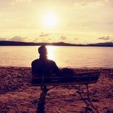 Homem novo sozinho na silhueta que senta-se em The Sun na praia Resto da tomada do turista no banco de madeira no lago do outono Fotos de Stock Royalty Free