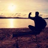 Homem novo sozinho na silhueta que senta-se em The Sun na praia Resto da tomada do turista no banco de madeira no lago do outono Fotografia de Stock
