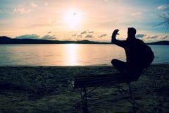 Homem novo sozinho na silhueta que senta-se em The Sun na praia Resto da tomada do turista no banco de madeira no lago do outono Fotografia de Stock Royalty Free