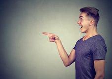 Homem novo surpreendido que aponta o dedo Imagens de Stock Royalty Free