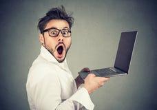 Homem novo surpreendido que guarda o portátil fotografia de stock royalty free