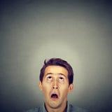 Homem novo surpreendido que olha acima Fotografia de Stock Royalty Free