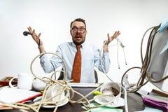 Homem novo tangled nos fios no local de trabalho imagens de stock