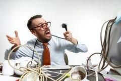 Homem novo tangled nos fios no local de trabalho foto de stock royalty free