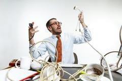 Homem novo tangled nos fios no local de trabalho foto de stock