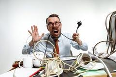 Homem novo tangled nos fios no local de trabalho fotos de stock
