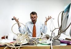 Homem novo tangled nos fios no local de trabalho imagem de stock royalty free
