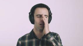 Homem novo triste que escuta a música em fones de ouvido vídeos de arquivo