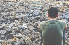 Homem novo triste que senta-se na terra estéril Procure um campo seco do arroz fotos de stock royalty free