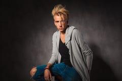 Homem novo triste que veste as calças de brim ásperas que levantam no fundo do estúdio foto de stock