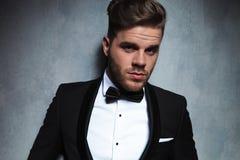 Homem novo unshaved atrativo com smoking preto e bowtie preto Imagem de Stock Royalty Free