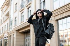 Homem novo urbano do moderno em uma camiseta encapuçado na moda com óculos de sol em um tampão preto com uma trouxa à moda em cur fotos de stock