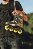 Homem novo urbano que guarda seus patins no ombro Imagem de Stock