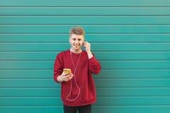 Homem novo vestindo os sweatshirtis vermelhos que escutam a música nos fones de ouvido e que olham uma câmera imagem de stock royalty free