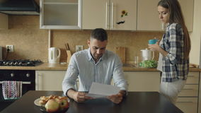 Homem novo virado que lê contas por pagar e abraçado por sua esposa que apoia o na cozinha em casa vídeos de arquivo