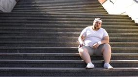 Homem obeso no sportswear que senta-se em escadas, falta da motivação para a perda de peso imagens de stock royalty free