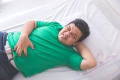 Homem obeso que tem a dor de estômago ao colocar em uma cama Fotografia de Stock Royalty Free