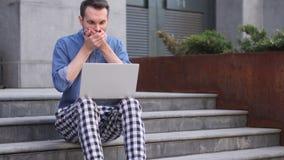 Homem ocasional chocado, chocado que usa o portátil ao sentar-se em escadas fora do escritório video estoque