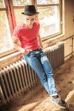 Homem ocasional com o chapéu que senta-se no calefator oxidado Fotos de Stock