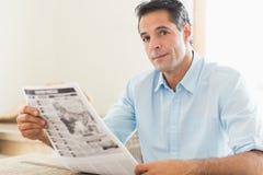 Homem ocasional com o jornal que olha afastado na cozinha imagens de stock royalty free
