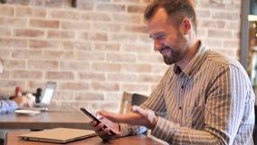 Homem ocasional da barba que comemora a vitória em Smartphone vídeos de arquivo