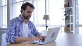 Homem ocasional da barba que trabalha no portátil no escritório, fim acima video estoque