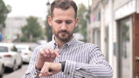 Homem ocasional da barba que usa Smartwatch exterior video estoque