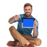 Homem ocasional de sorriso que sitiing com tabuleta e apontar o dedo imagens de stock royalty free