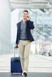 Homem ocasional do negócio no telefonema na estação com mala de viagem Fotografia de Stock Royalty Free