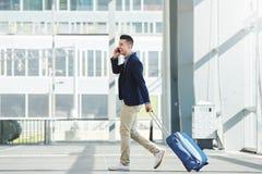 Homem ocasional do negócio que anda na estação com telefone e mala de viagem Imagens de Stock Royalty Free