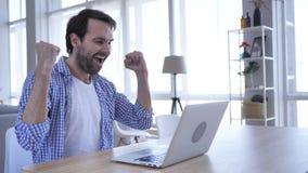 Homem ocasional excitado da barba que comemora o sucesso, trabalhando no portátil vídeos de arquivo
