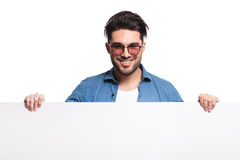 Homem ocasional feliz que guarda uma placa branca Foto de Stock Royalty Free