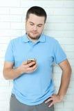 Homem ocasional feliz que usa o smartphone que está a parede de tijolo próxima Pensamento considerável novo do homem Imagem de Stock Royalty Free
