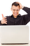 Homem ocasional forçado com os vidros que olham o portátil Foto de Stock Royalty Free