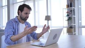 Homem ocasional irritado virado da barba que trabalha no portátil no escritório vídeos de arquivo