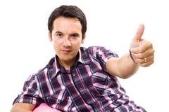 Homem ocasional novo assentado em um sofá cor-de-rosa pequeno Imagens de Stock Royalty Free