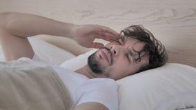 Homem ocasional novo cansado com a dor de cabeça que encontra-se na cama video estoque