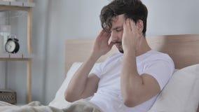 Homem ocasional novo cansado com a dor de cabeça que senta-se na cama filme
