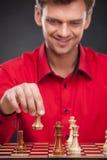 Homem ocasional novo que senta-se sobre a xadrez Fotografia de Stock Royalty Free