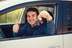 Homem ocasional novo que veste chaves azuis do carro da terra arrendada da camisa fora da janela, mostrando o polegar acima do ge fotografia de stock royalty free