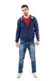 Homem ocasional novo tenso na camiseta encapuçado azul que olha a câmera cepticamente foto de stock royalty free